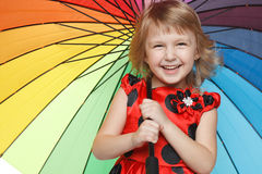 Girl standing under colorful umbrella Stock Image