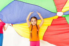 Girl standing under parti-colored parachute canopy. Portrait of preschool girl standing under the tent made of parti-colored parachute with her hands up Royalty Free Stock Photography