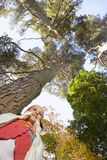 Girl standing under tall tree Royalty Free Stock Photo