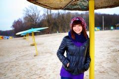 Girl standing under an umbrella on the beach in autumn Stock Photo