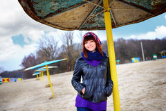 Girl standing under an umbrella on the beach in autumn Stock Images