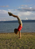 Girl standing upside down 2. Cute girl relaxing doing stand up (standing upside-down) near the Adriatic sea. Croatia-Dalmatia. Vertical color photo royalty free stock images