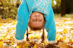 Girl standing upside down. Portrait of a girl standing upside down in autumnal park Stock Photos