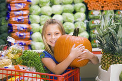 Girl (7-9) standing in vegetable section of supermarket, clutching large pumpkin, smiling, portrait Royalty Free Stock Photography
