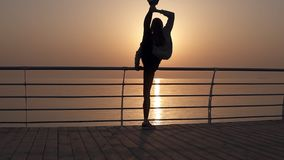 Girl standing in a vertical twine. Arching. Stretches out near the sea ocean with a beautiful sun panorama.  stock video