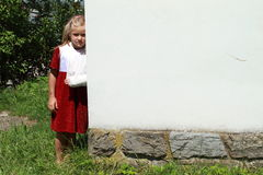 Girl standing by a wall. Barefoot little girl that is standing by a wall stock photos