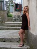 Girl standing by the wall. Girl in black miniskirt standing by the wall Royalty Free Stock Photos