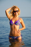 Girl standing in the water. Blondie with black sunglasses posing standing in the water Stock Photography