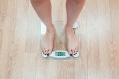 The girl standing on weigher Stock Images