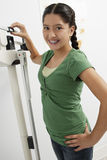 Girl Standing On Weighing Machine Royalty Free Stock Images