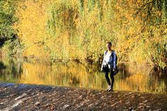 Girl standing on weir. Tropical girl - young Papuan woman standing in water on weir of river Malse with colorful autumn trees behind in Rimov, Czech Republic Royalty Free Stock Photography