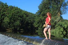 Girl standing on the weir Stock Photo
