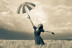 Girl is standing on a wheat field with umbrella royalty free stock image