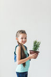 Girl standing on a white background with a plant on Earth Day.  Royalty Free Stock Photo