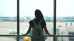 Girl standing at the window in the airport lounge.  stock footage