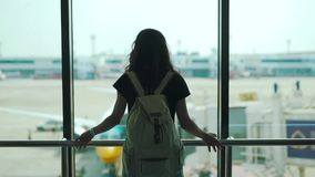 Girl standing at the window in the airport terminal stock video