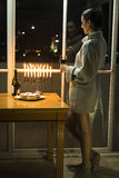 A girl standing by the window with the menorah celebrating Hanukkah. Stock Photo