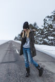 Girl is standing on the winter road Stock Photography