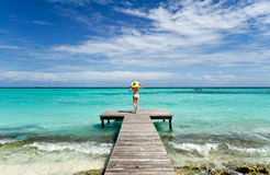 Girl standing on wooden bridge extended into the s Royalty Free Stock Image