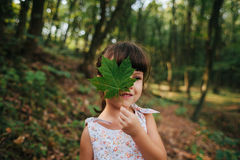 Girl standing in the woods holding a leaf in his hands. hidden b Royalty Free Stock Images