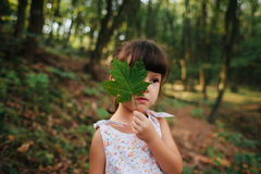 Girl standing in the woods holding a leaf in his hands. hidden b Royalty Free Stock Photo