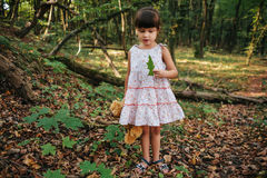 Girl standing in the woods holding a toy bear in hand Royalty Free Stock Images