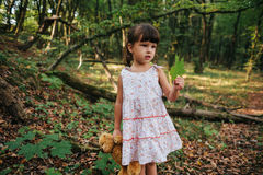 Girl standing in the woods holding a toy bear in hand Stock Images