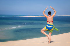 Girl in a standing yoga pose in the beach Stock Photography