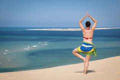 Girl in a standing yoga pose in the beach Royalty Free Stock Images