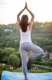 Girl standing in a yoga pose with returning to the Sun Stock Images