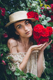 Girl stands against a background bushes with red roses Stock Photos