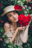 Girl stands against a background bushes with red roses Royalty Free Stock Photos