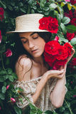 Girl stands against a background bushes with red roses Stock Image