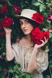 Girl stands against a background bushes with red roses Royalty Free Stock Image