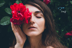 Girl stands against a background bushes with red roses Stock Photography