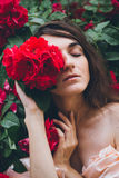 Girl stands against a background bushes with red roses Royalty Free Stock Photo
