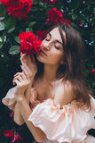 Girl stands against a background bushes with red roses Stock Images