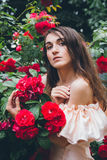 Girl stands against a background bushes with red roses Stock Photo