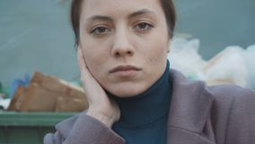The girl stands against the background of trash. Face close up. Slow stock footage