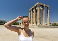 Girl stands against the ruins of the ancient temple of Olympian Stock Photos
