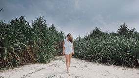 Girl Stands Against The Background Of Exotic Plants On The Beach