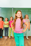 Girl stands with arms on hips near blackboard Royalty Free Stock Photos