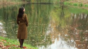 Girl Stands At Autumn Lake stock video