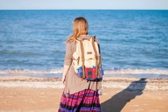 A girl stands back and looks at the sea. Hippie Girl looks at the sea. Woman with a bottle of wine is by the sea. hippie Stock Photo