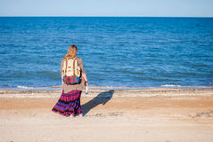 A girl stands back and looks at the sea. Hippie Girl looks at the sea. Woman with a bottle of wine is by the sea. hippie Royalty Free Stock Image