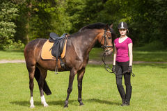 Girl stands besides her horse Royalty Free Stock Images