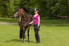 Girl stands besides her pony Stock Images