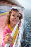 Girl stands on board of ship, clings to railing Royalty Free Stock Photo