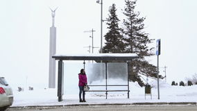 A girl stands at the bus stop in winter stock video