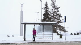 A girl stands at the bus stop in winter stock video footage